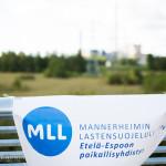 MLL:n banneri, taustalla kosteikkoa ja voimalaitos. Kuva: Tuomas Heinonen